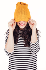 Happy autumn or winter girl covering face with wool cap