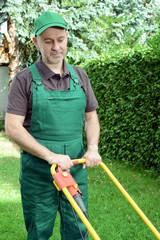 Gärtner bei Gartenpflege mit Rasenmäher