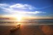 Leinwanddruck Bild - Amazing sunset on the ocean beach, canoe lying on the shore.