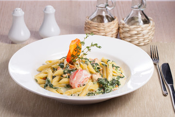 pasta with spinach on dish and wooden table
