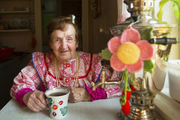 Mature positive woman in folk costume drinking tea in his house.