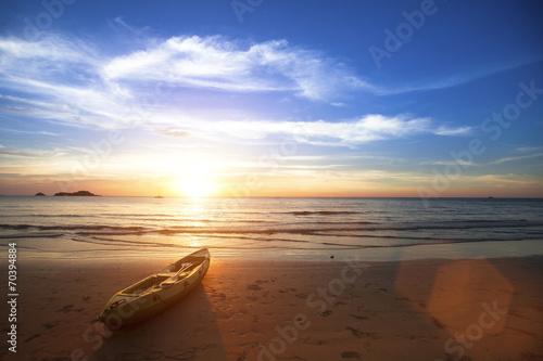 Leinwanddruck Bild Amazing sunset on the ocean beach, canoe lying on the shore.
