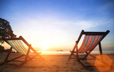 Pair beach loungers on the deserted coast sea at sunrise.