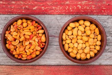 two bowls of peanuts on rustic wood background