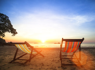 Loungers on deserted coast sea at sunrise.