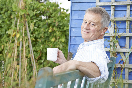 Senior Man Relaxing In Garden With Cup Of Coffee - 70395215