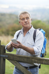 Senior Man Checking Location With Mobile Phone On Hike