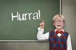 """Kind vor der Tafel """"Hurra"""""""