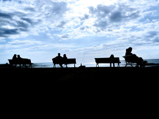 silhouette people bench sea
