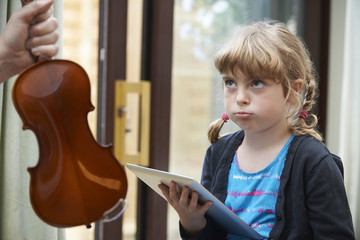 Young Girl Would Rather Play On Digital Tablet Than Practise Vio