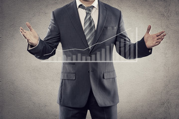 Portrait of man in business suit presenting trade chart
