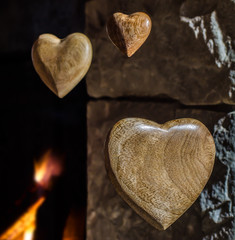 Wooden hearts floating with a stone fireplace