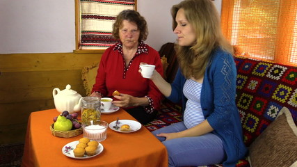 Senior grandma and young granddaughter eat sweets with tea