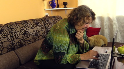 Old grandmother woman working with laptop notebook computer