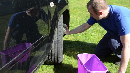 young man clean wash his favourite car wheel with soap on grass
