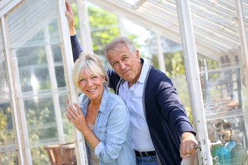 Senior couple standing by greenhouse in garden