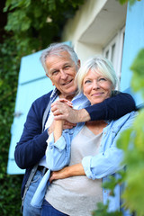 Senior man embracing his wife at house front door