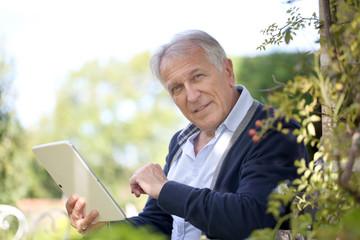 Senior man websurfing on tablet in home garden