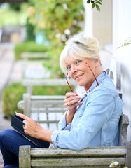 Senior woman reading book sit on bench
