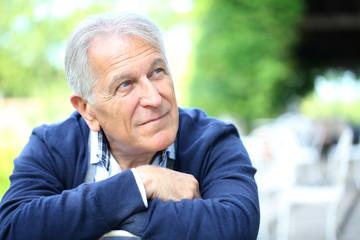 Portrait of senior man sitting in home garden