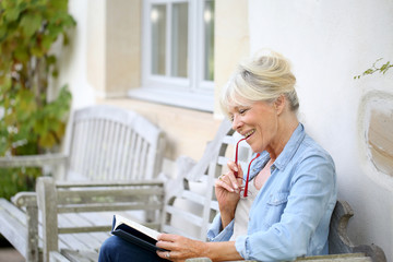 Senior woman reading book sit on bench