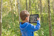 child in the woods with the tablet pc