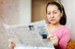 serious mature woman reading newspaper