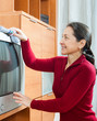 mature woman dusting TV at living room