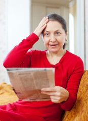 grief mature woman with newspaper