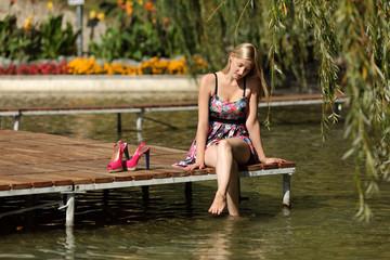 Dziewczyna, blondynka wypoczywa nad wodą.