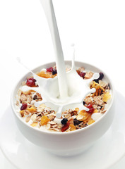 Milk splashing into a bowl of fresh muesli