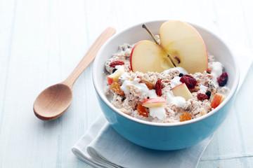 Bowl of muesli, apple, fruit, nuts and milk