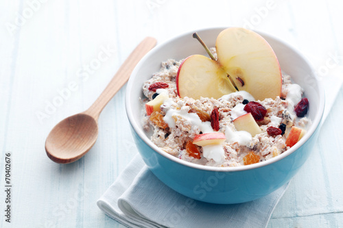 Bowl of muesli, apple, fruit, nuts and milk