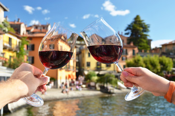 Two wineglasses in the hands. Varenna town at the lake Como, Ita