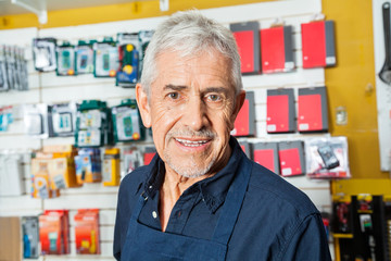 Confident Senior Worker Smiling In Hardware Shop