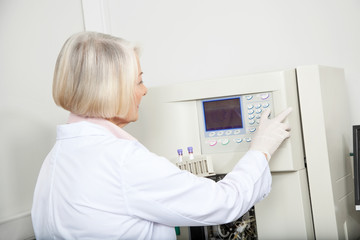 Scientist With Samples Operating Analyzer In Lab