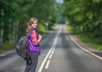 Beautiful girl with backpack walking on the road