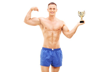 Bodybuilder holding a golden trophy