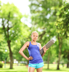 Female athlete holding an exercising mat in park