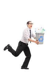 Man running with a recycle bin in his hands