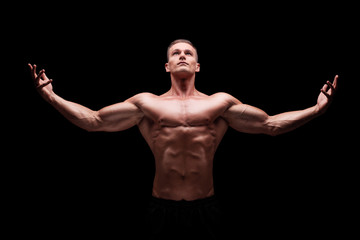 Muscular man gesturing with hands and looking up
