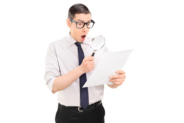 Shocked man looking at document through magnifier