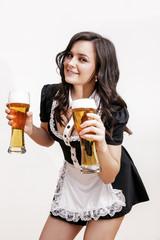 junge, hübsche Frau in Dirndl hält Biergläser