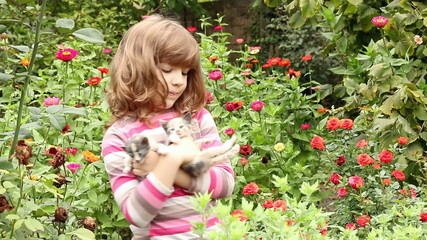 little girl hold two kittens