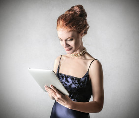 Elegant woman reading from a tablet