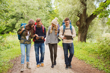 group of friends with backpacks and tablet pc