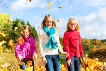 Schwestern toben im Herbst Laub