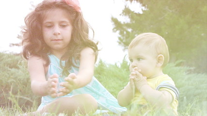 Cute girl and her little brother having fun with soap bubbles