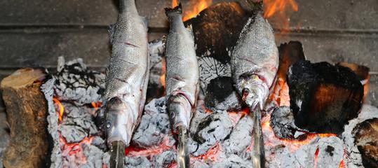 Cooking fish grilled over hot coals bonfire
