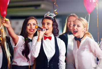group of girls friends having fun on karaoke party